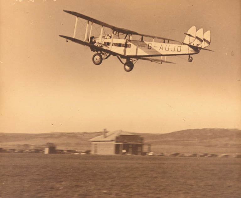 A vintage gelatin silver photograph (254 x 318 mm) of the West Australian Airways De Havilland DH-66 Hercules biplane G-AUJO, taking off from what may be Adelaide's Parafield Airport. Aviation.