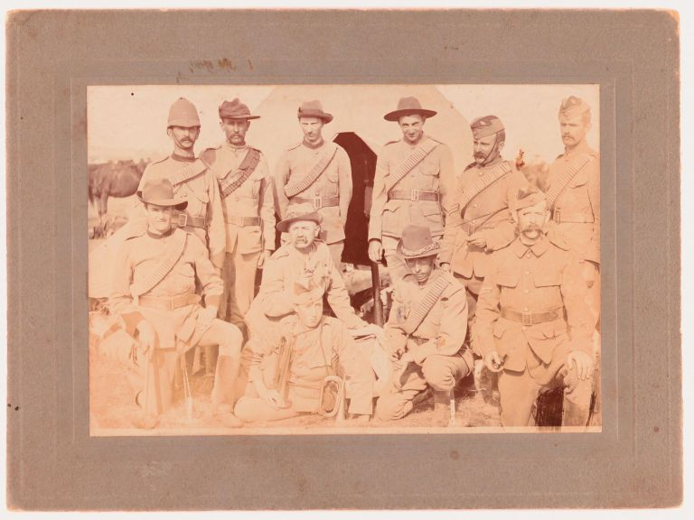 A vintage high-gloss gelatin silver photograph (100 × 145 mm) of a group of eleven Australian soldiers posed in front of a tent, possibly members of the (Third) 'Bushmen's Contingent at Camp, Langwarrin', Victoria, in late 1899. The photograph is slightly marked, with light uneven discolouration; the original blind-decorated mount is a little marked. The ink stamp of a Melbourne photographer on the verso (R. McGeehan, 96 Albert St., Windsor) provided a clue to placing the image firmly in space and time; the pencilled initials L.E.S. may eventually provide useful too. Boer War.