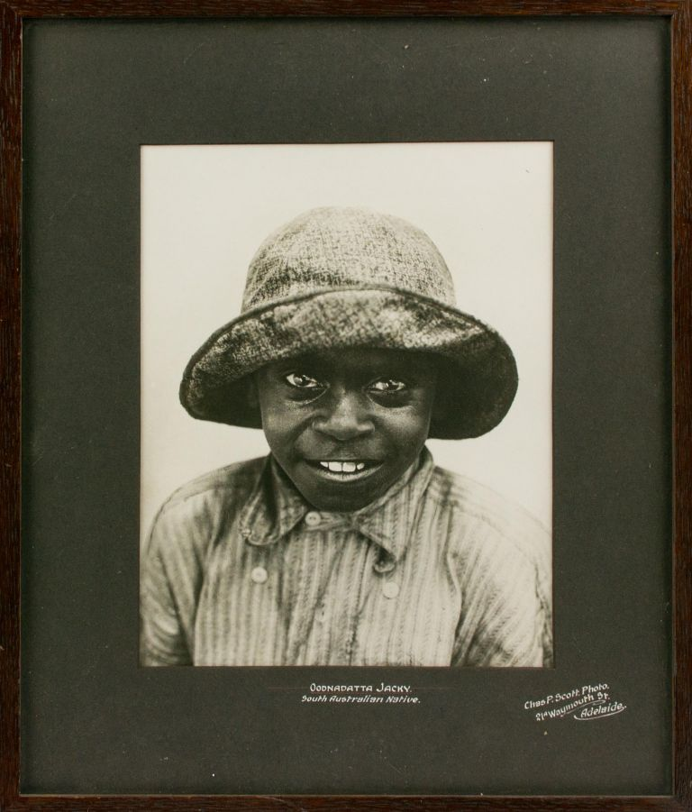 'Oodnadatta Jacky - South Australian Native'. A charming vintage portrait photograph of a young Aboriginal boy wearing a large cloth hat and an even bigger grin. Indigenous Australian Portraiture, Charles P. SCOTT.