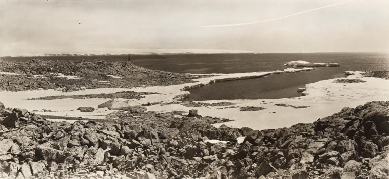 A panoramic view of Cape Denison, showing the Winter Quarters of the Australasian Antarctic Expedition, 1911-1914, but taken during the British, Australian and New Zealand Antarctic Research Expedition, 1929-31. Frank HURLEY.