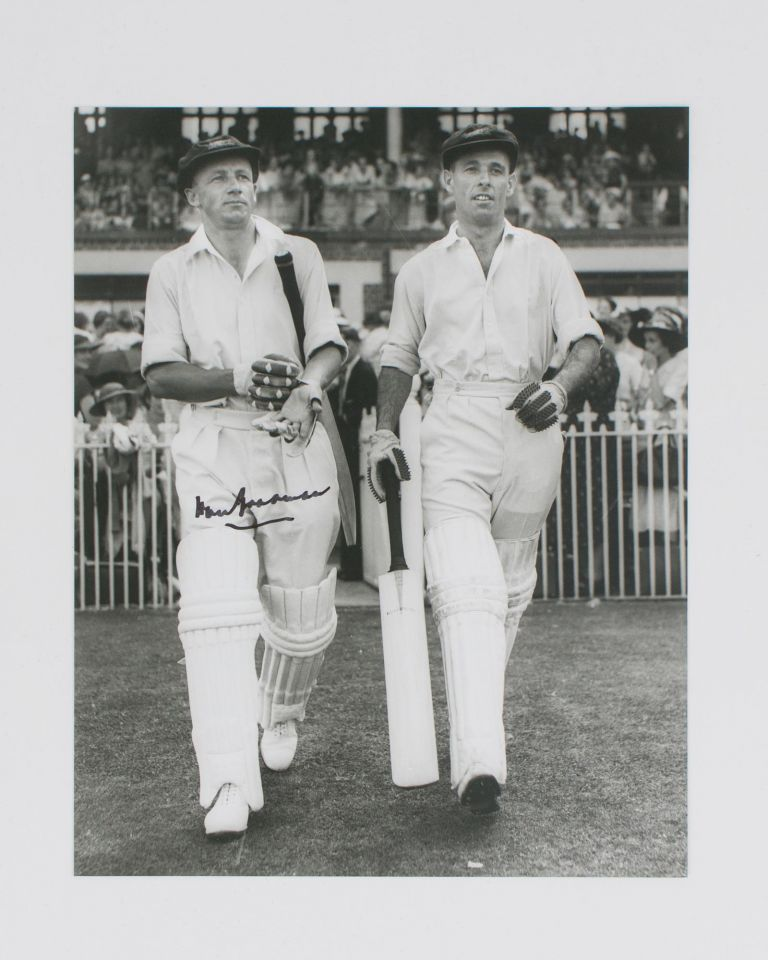 A signed photograph (black and white, 253 × 203 mm) of Don Bradman walking out to bat with Jack Fingleton. Cricket, Don BRADMAN.