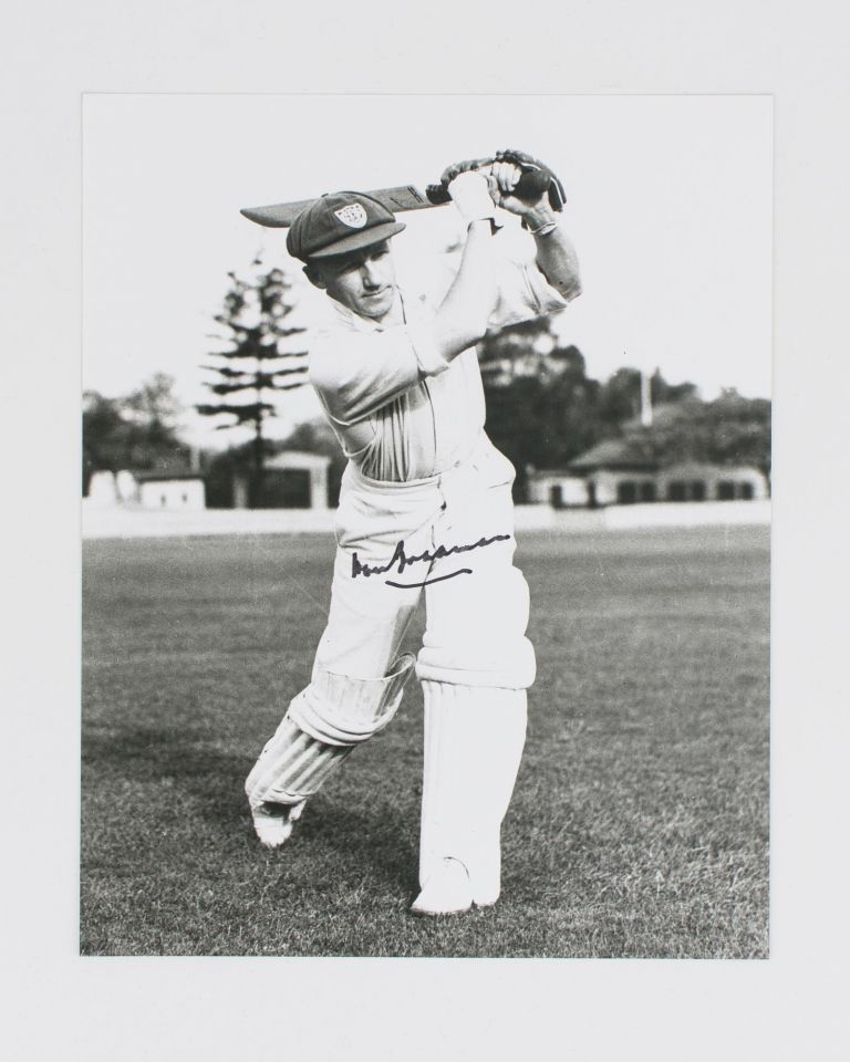 A signed photograph (black and white, 253 × 203 mm) of Don Bradman executing a straight drive. Cricket, Don BRADMAN.
