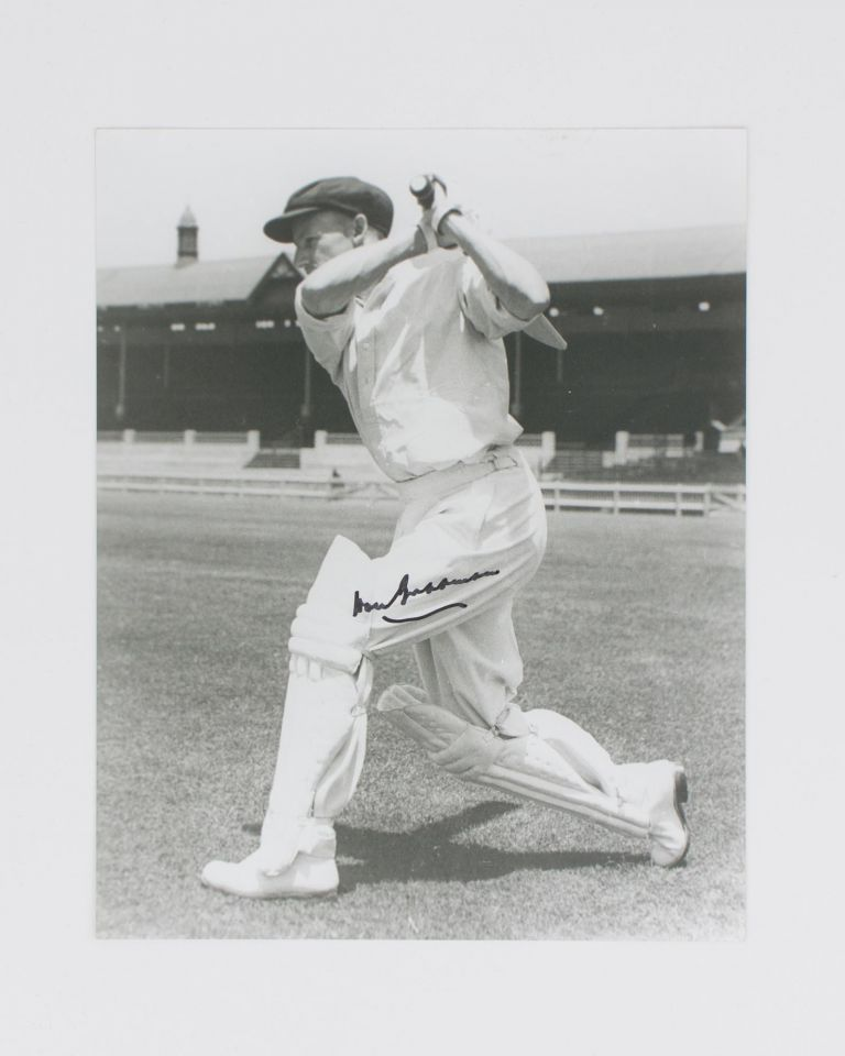 A signed photograph (black and white, 253 × 203 mm) of Don Bradman executing a cover drive. Cricket, Don BRADMAN.