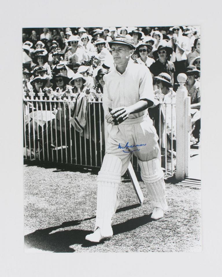 A signed photograph (black and white, 303 × 240 mm) of Don Bradman walking out to bat. Cricket, Don BRADMAN.