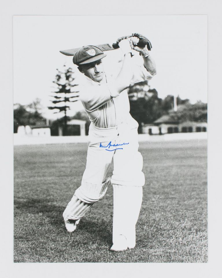 A signed photograph (303 × 240 mm) of Don Bradman executing a straight drive. Cricket, Don BRADMAN.
