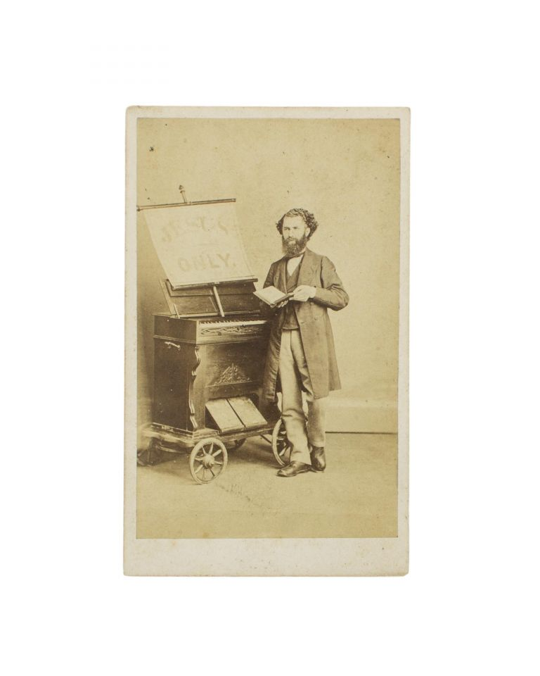 A carte de visite of a musician and his small portable organ on a four-wheeled trolley. Street Musician.