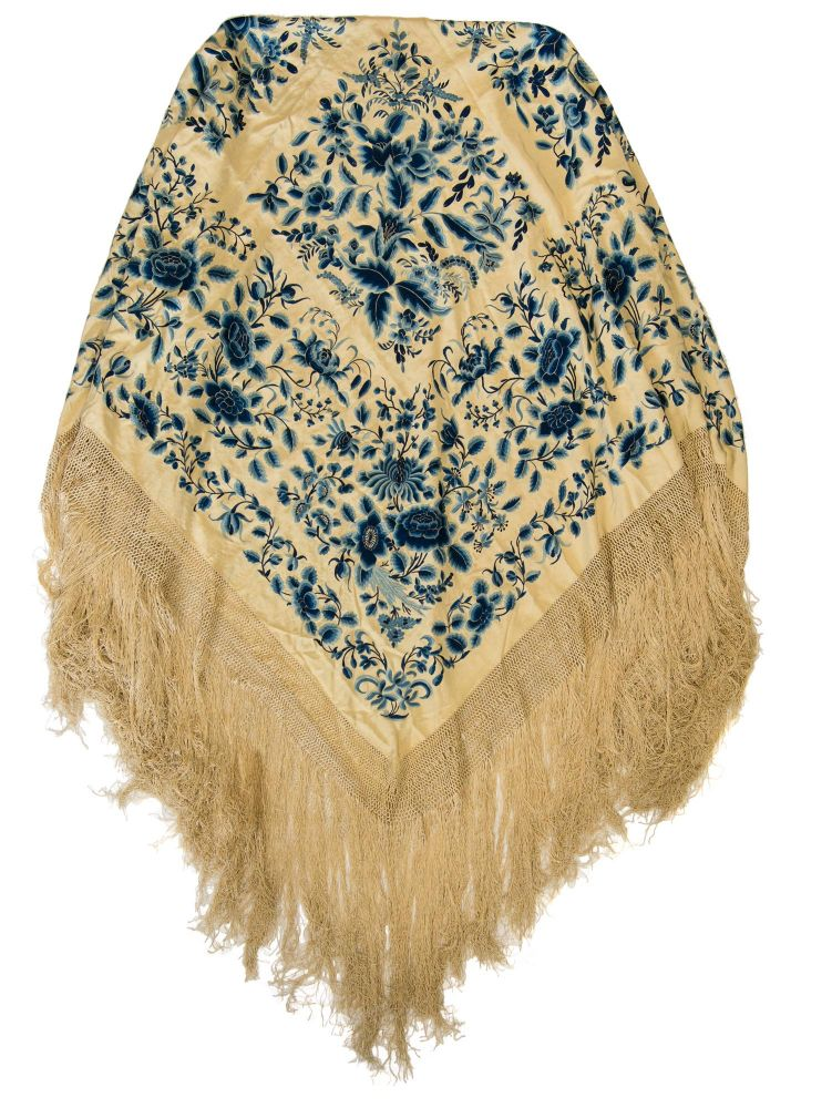 A very large embroidered silk piano shawl or Manila shawl. The cream silk ground is elaborately hand-embroidered on both sides with blue silks in a floral design, and is edged with a knotted silk border and thick, heavy fringe