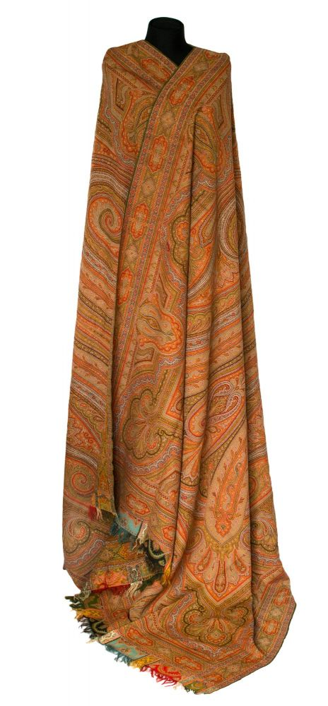 A large Kashmir-style paisley shawl of woven wool, with harlequin borders and fringes to the short ends
