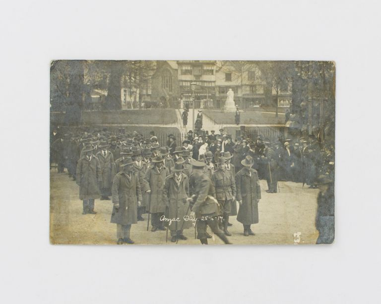 A postcard-format gelatin silver photograph of an Anzac Day commemoration in England in 1917. A sombre group of Australian walking wounded features prominently. 1917 Anzac Day.
