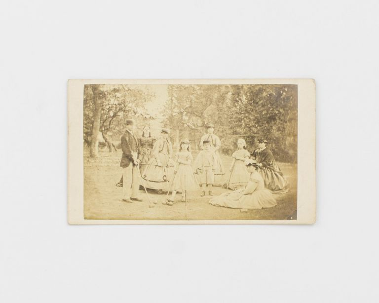 A carte de visite of a large Victorian-era family group on a croquet court. Various members are holding mallets; two balls and a hoop are included for good measure. Croquet.
