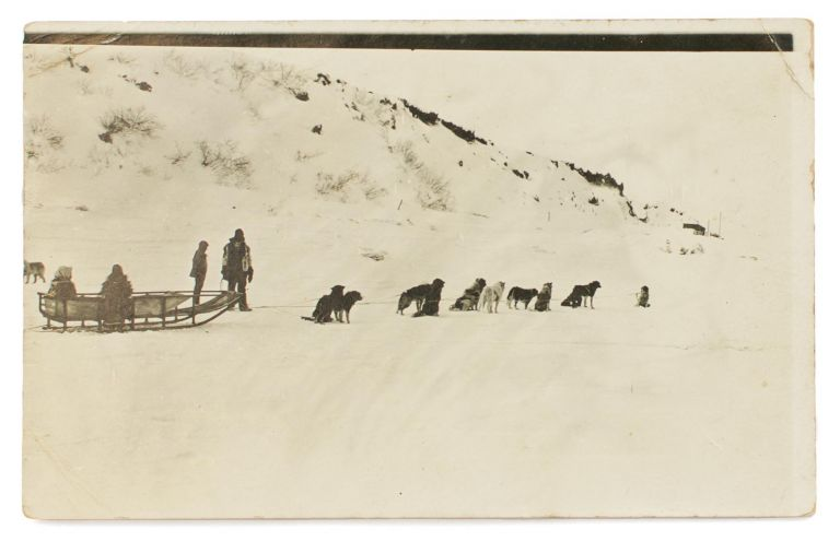 A postcard-format gelatin silver photograph of a dog-sled, with passengers and handlers, addressed to 'Miss Paquita Delprat | Adelaide | S. Australia'. Australasian Antarctic Expedition, Andrew WATSON.