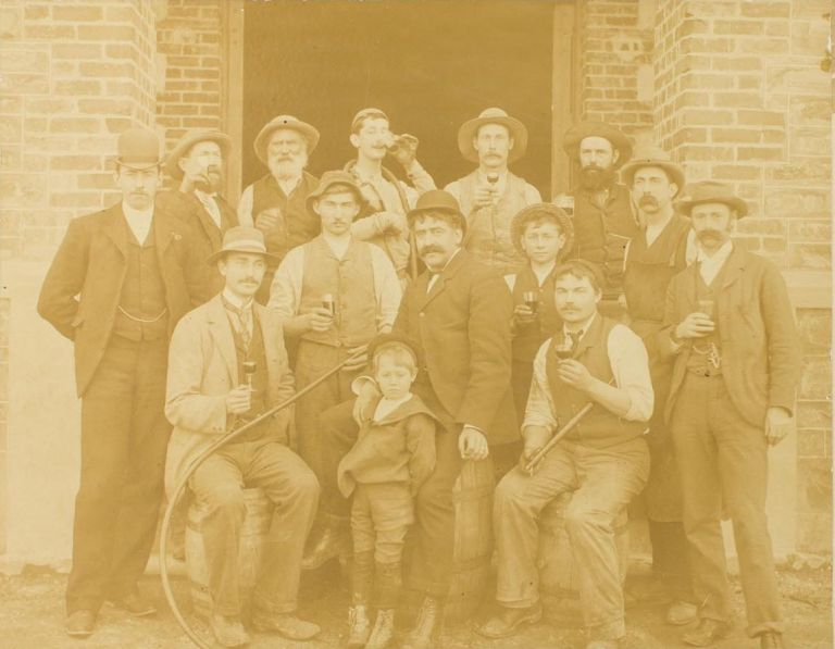 A vintage photograph of staff at Chateau Tanunda Winery in the Barossa Valley, South Australia; most of them are raising glasses of house wine, and those seated are on barrels. Barossa Valley.