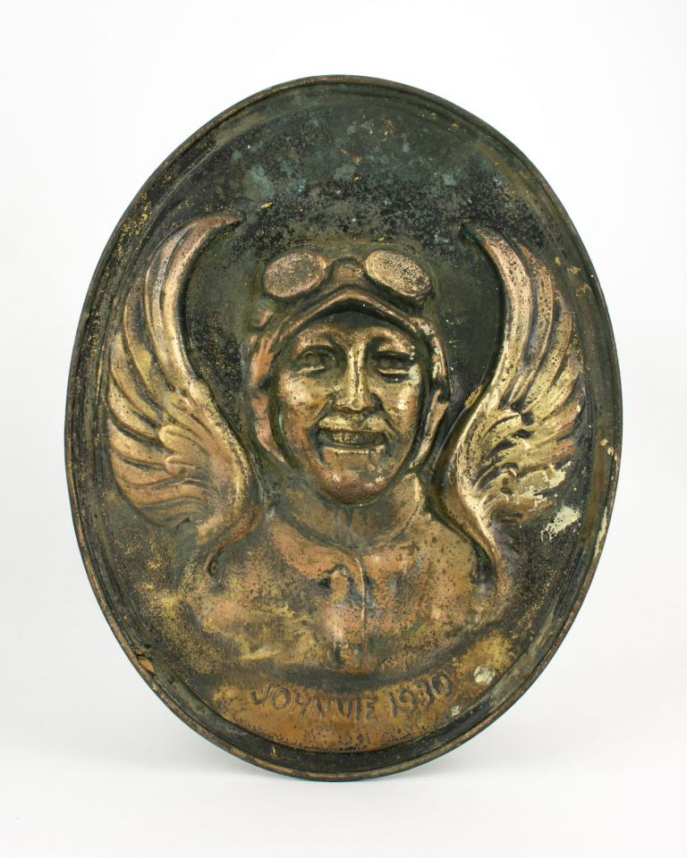 A hand-crafted and possibly unique relief portrait (in pressed and hand-chased brass) of the pioneering pilot Amy Johnson, lettered 'Johnnie 1930', most likely produced to commemorate her record-breaking flight from England to Australia in that year. Amy JOHNSON.