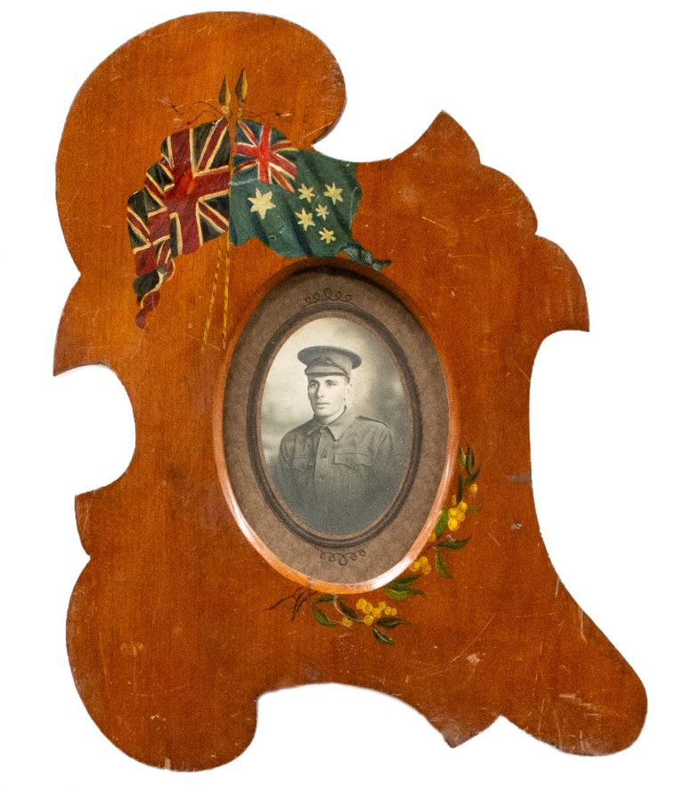 A handmade picture frame with patriotic Australian motifs, containing the photograph of an unidentified Australian soldier from the First World War. Commemoration.