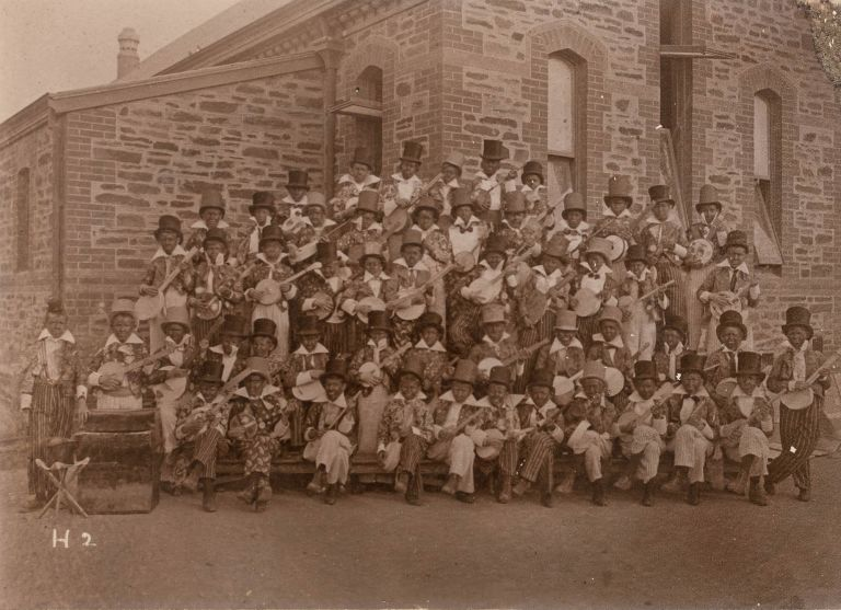 A group photograph of young lads in blackface, dressed as minstrels with banjos. Photography, Racial Stereotyping.