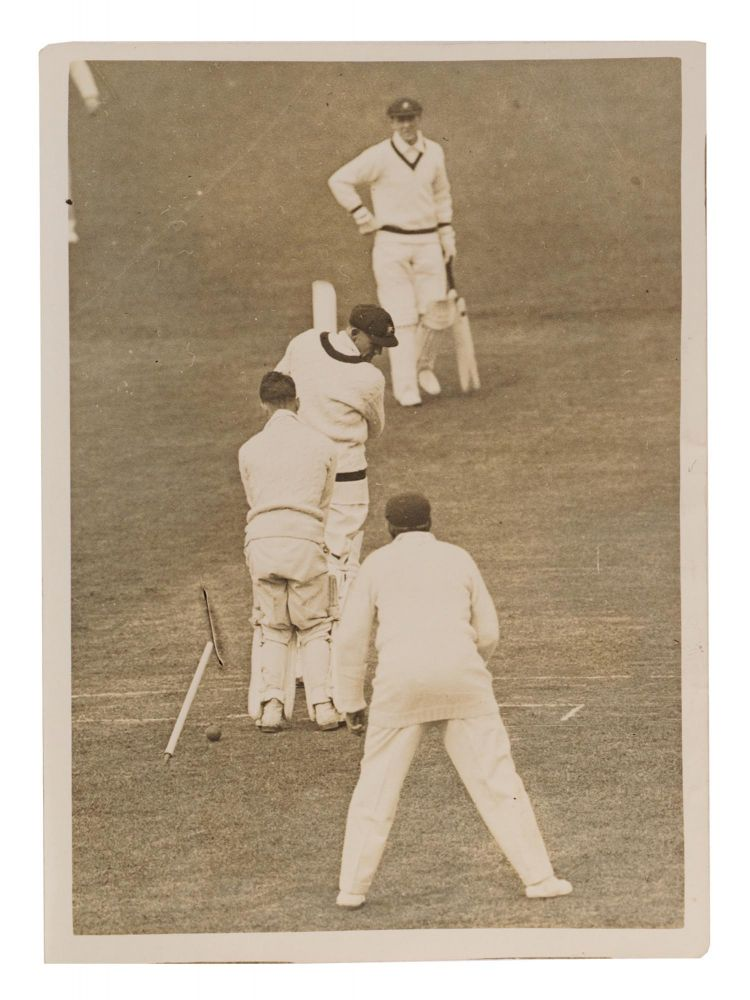 An original vintage gelatin silver press photograph (120 x 165 mm), with a typed caption mounted on the verso: 'Australians dismissed for 156 runs in their first innings against Essex at Leyton. Fairfax (Australia) loses his leg stump to Palmer after scoring 12 runs'. Cricket, Archibald JACKSON, 'Archie', New South Wales and Australia.