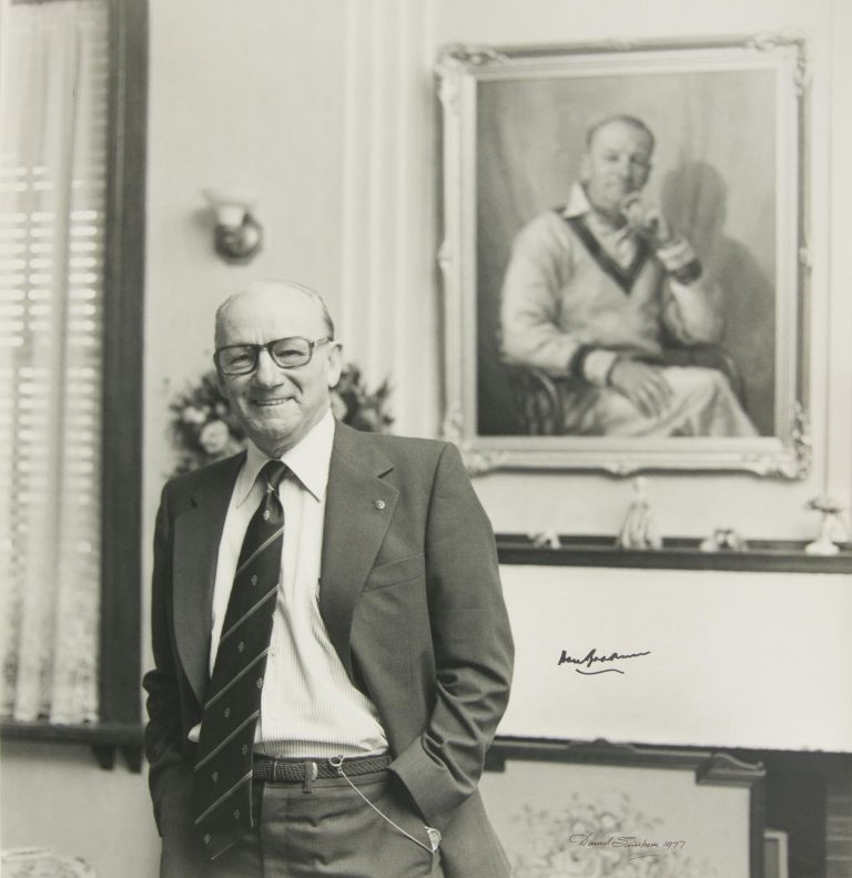 A masterly 1977 portrait by the Adelaide photographer David Simpson, featuring a distinguished but relaxed Sir Don at home, standing in front of his familiar portrait in oils. Cricket, Sir Donald BRADMAN.