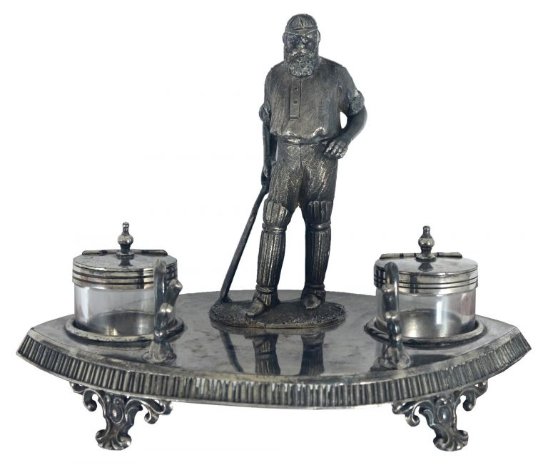A silver-plated standish - a stand holding pens and ink - comprising an almond-shaped base (approximately 195 x 130 x 30 mm), surmounted by a 120 mm-high figure of W.G. Grace standing between two silver-lidded glass inkpots and a two-part stand for pens. Probably Edwardian; the underside of the base is stamped 'James Deakin & Sons / Sheffield / 10475'. The decorated rim of the base is slightly bumped; overall it is in excellent condition. Cricket, W. G. GRACE.