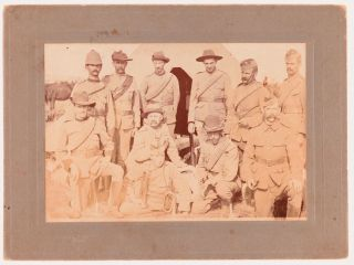 A vintage high-gloss gelatin silver photograph (100 x 145 mm) of a group of eleven Australian soldiers posed in front of a tent, possibly members of the (Third) 'Bushmen's Contingent at Camp, Langwarrin', Victoria, in late 1899. The photograph is slightly marked, with light uneven discolouration; the original blind-decorated mount is a little marked. The rubber-stamp of a Melbourne photographer on the verso (R. McGeehan, 96 Albert St., Windsor) provided a clue to placing the image firmly in space and time; the pencilled initials L.E.S. may eventually provide useful too. Boer War.