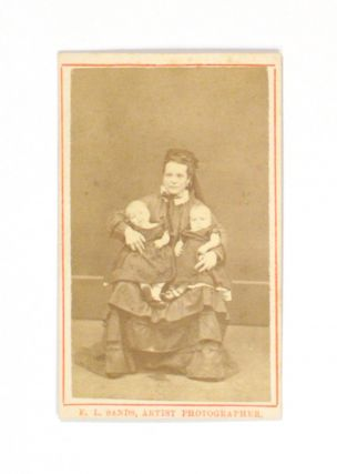 An albumen paper carte de visite photograph of a young woman holding twin baby girls. Portrait of...