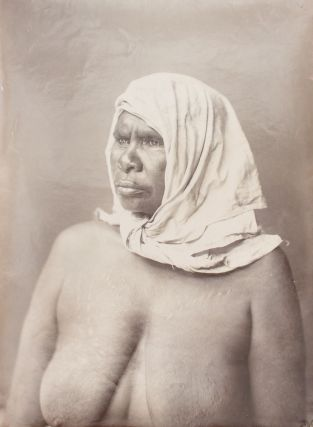 A fine portrait of an Indigenous Australian woman wearing a plain head-scarf knotted under her...