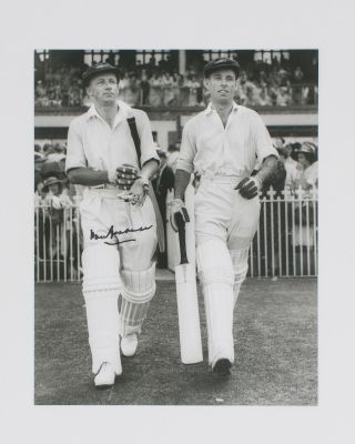 A signed photograph (black and white, 253 × 203 mm) of Don Bradman walking out to bat with Jack...