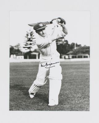 A signed photograph (black and white, 253 × 203 mm) of Don Bradman executing a straight drive....
