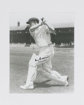 A signed photograph (black and white, 253 × 203 mm) of Don Bradman executing a cover drive....