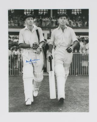 A signed photograph (black and white, 303 × 240 mm) of Don Bradman walking out to bat with Jack...