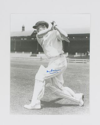 A signed photograph (black and white, 303 × 240 mm) of Don Bradman executing a cover drive....
