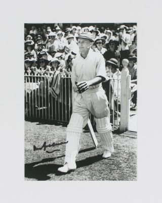A signed photograph (black and white, 177 × 125 mm) of Don Bradman executing a cover drive....
