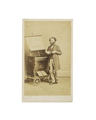 A carte de visite of a musician and his small portable organ on a four-wheeled trolley. Street...