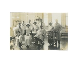A vintage photograph of a hospital operating theatre, complete with nine doctors and nurses - and...