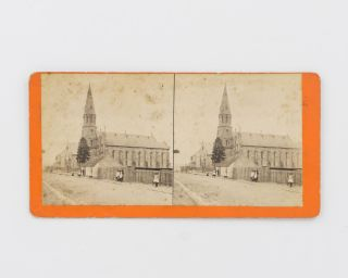 A stereophotograph of an unidentified streetscape with a large church, captioned on the rear of...
