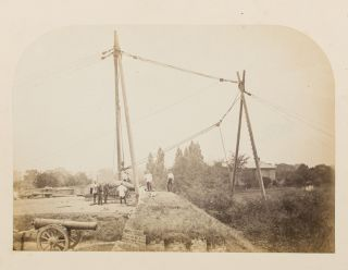 A vintage photograph showing a very large artillery piece being manoeuvered into position with an intricate block-and-tackle system