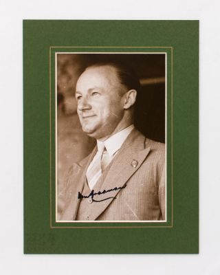 A signed portrait photograph of Don Bradman smartly attired in a three-piece business suit....