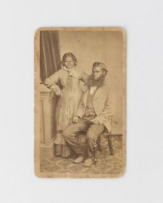 A carte de visite portrait photograph of an Indigenous man and woman in a classic studio setting...